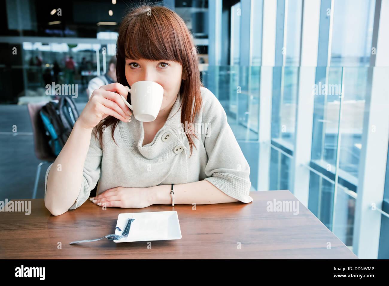 Donna di bere il caffè in tazza in un cafe Immagini Stock