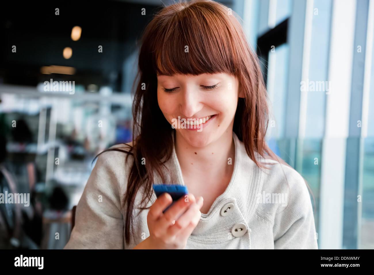 La donna gli sms sul cellulare e sorridente, seduti in un caffè Immagini Stock