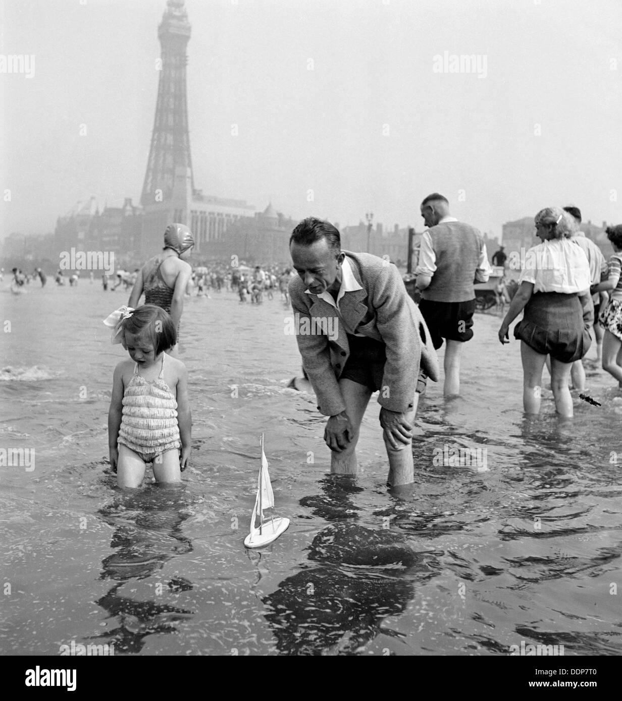 Un padre e figlia vela un modello di yacht in mare, Blackpool, c1946-1955. Artista: John Gay Immagini Stock