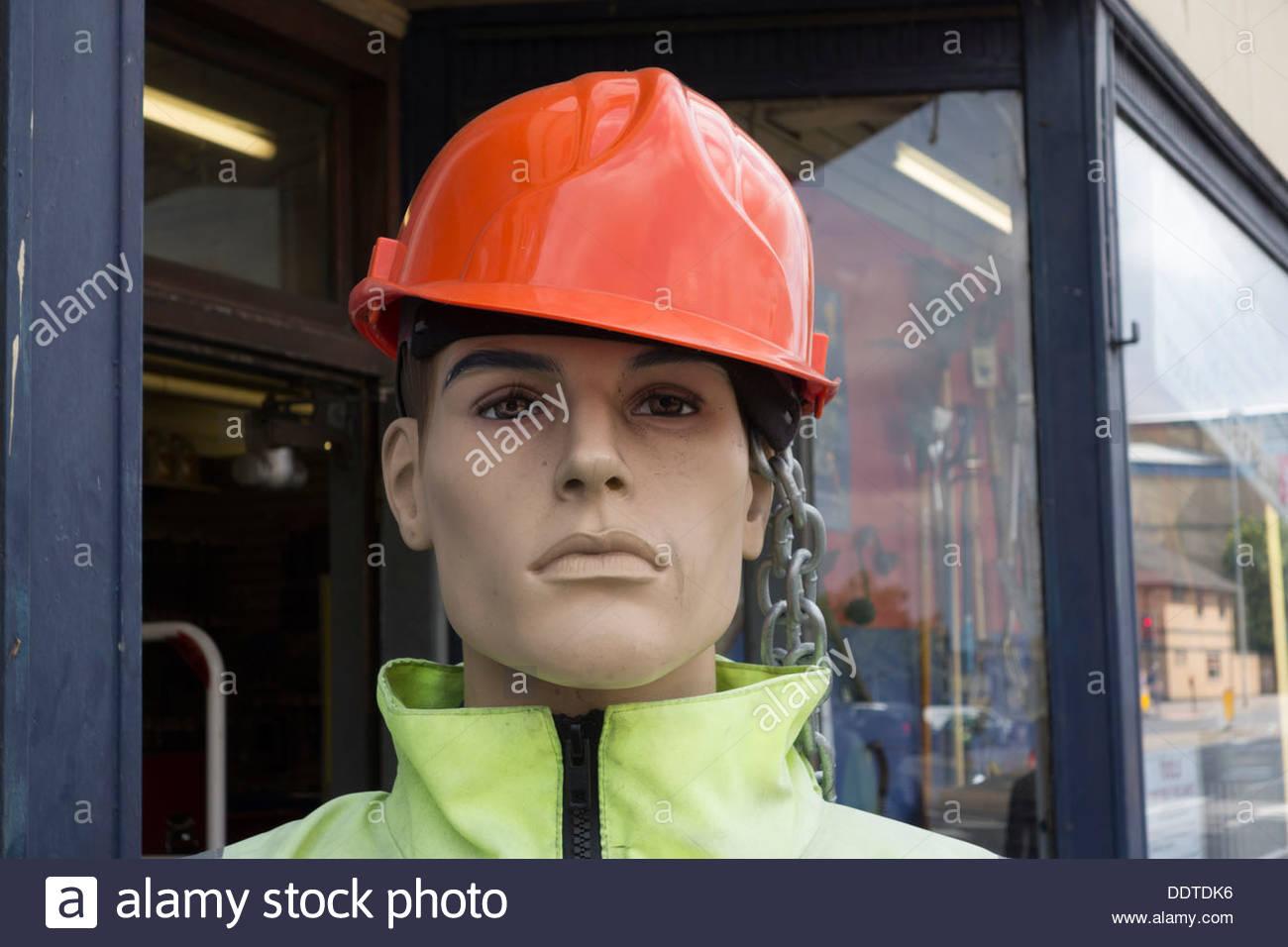Modello incatenato al di fuori di un utensile di mercanti, vestito di un casco di sicurezza e una elevata visibilità camicia Immagini Stock