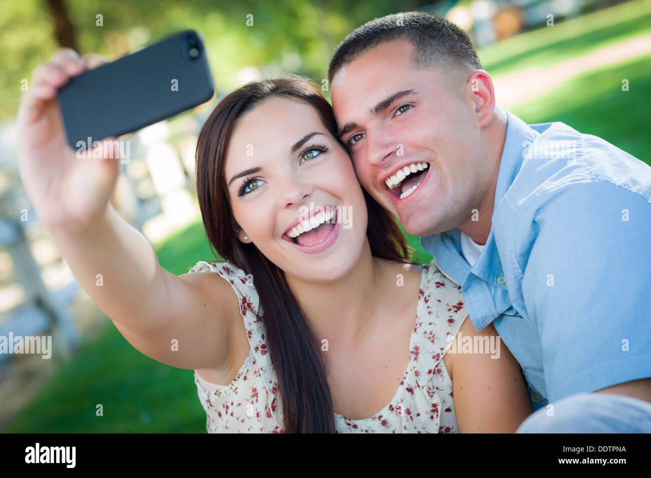Felice razza mista giovane tenendo Autoritratto con uno Smart Phone nel parco. Immagini Stock