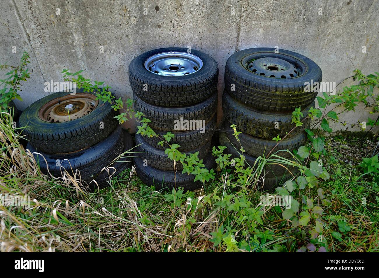 Vecchia auto pneumatici tra ortiche, Schaeftlarn, Bavaria Foto Stock