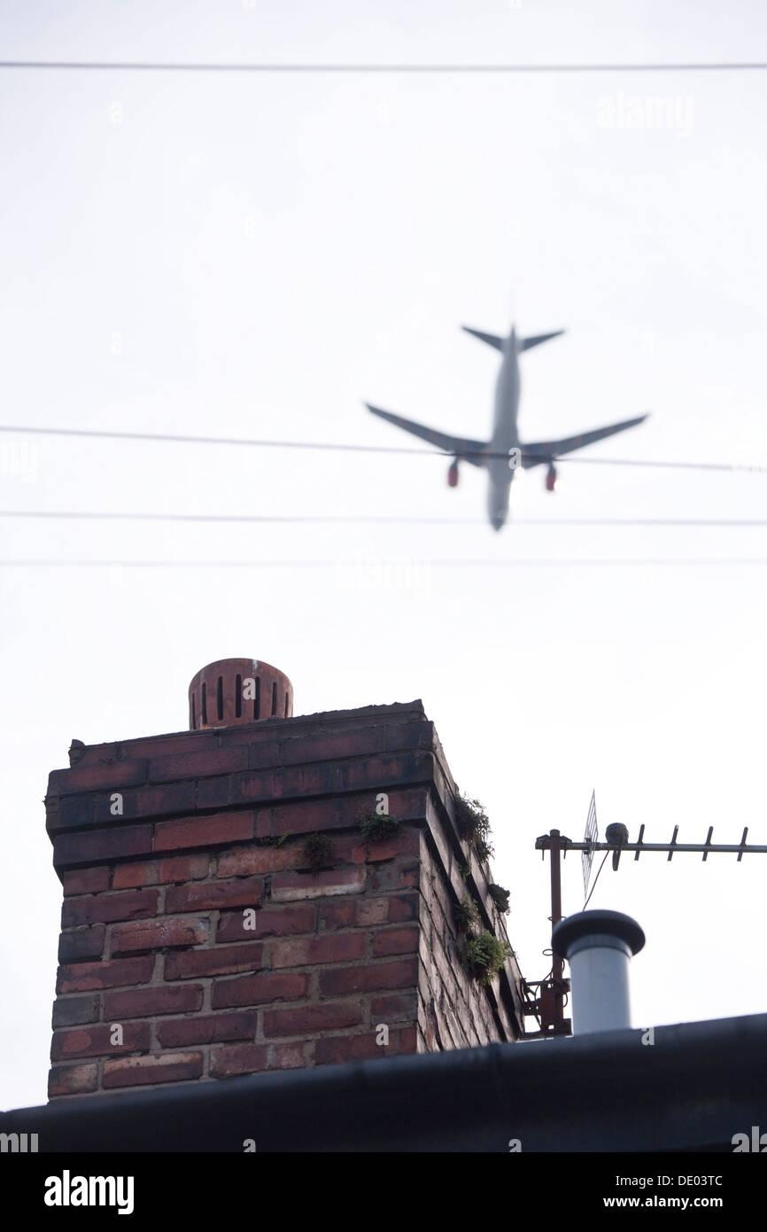 Aeroplano volando a bassa quota sopra la casa superiore del tetto. Immagini Stock