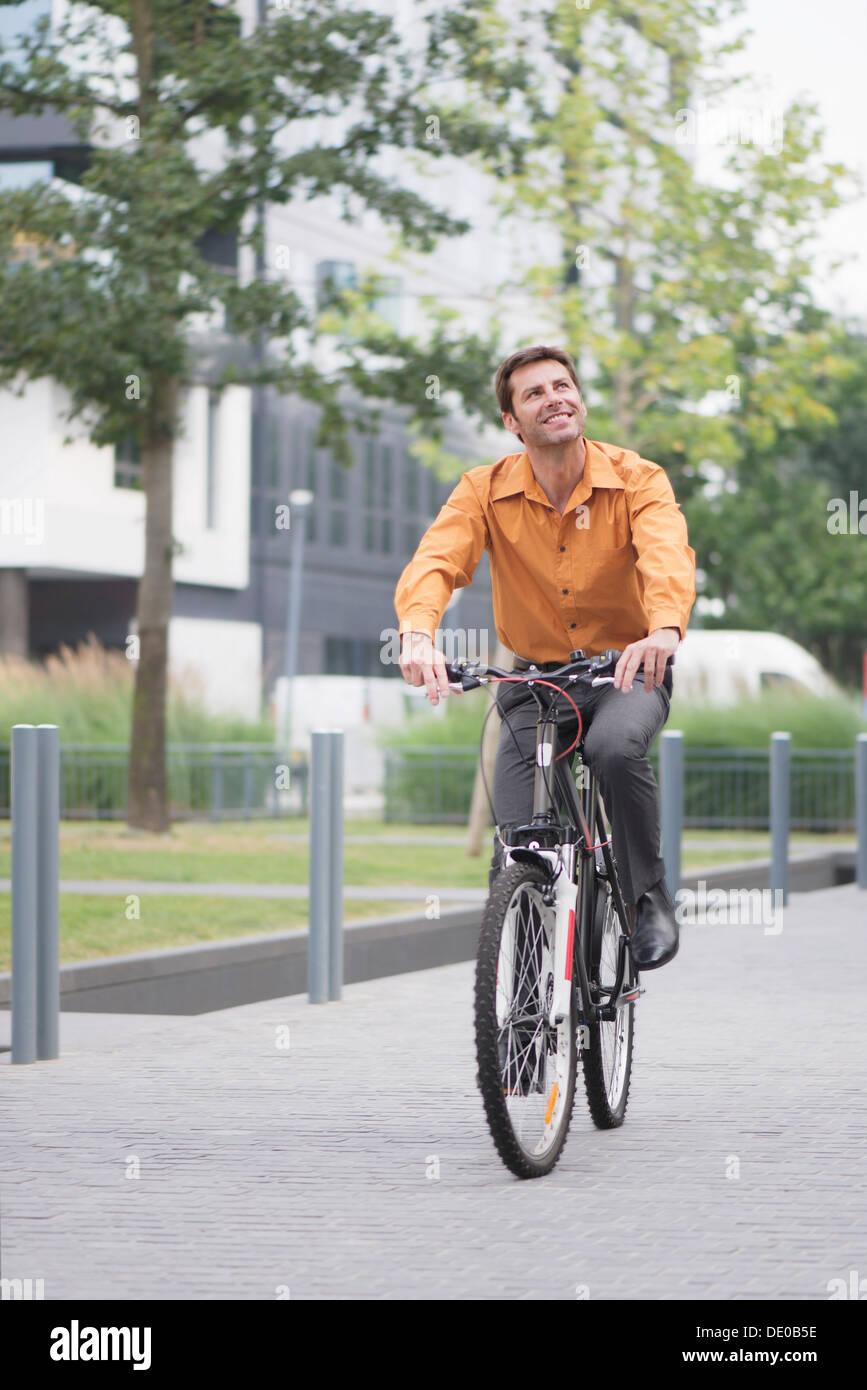 Uomo in abbigliamento business Bicicletta Equitazione Immagini Stock