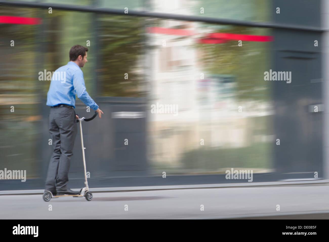 Uomo in abbigliamento business a cavallo su scooter push Immagini Stock