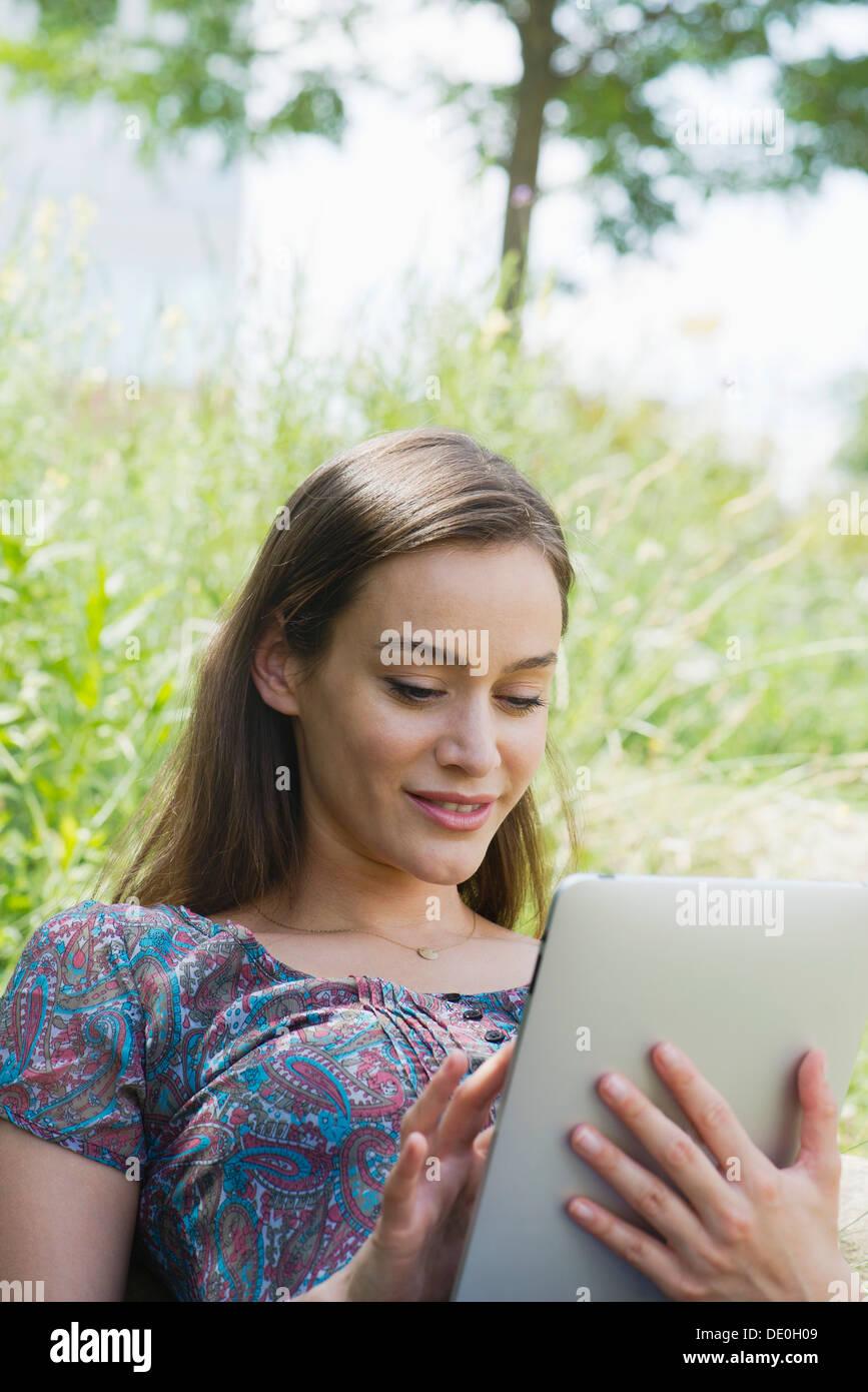 Donna con tavoletta digitale all'aperto Immagini Stock