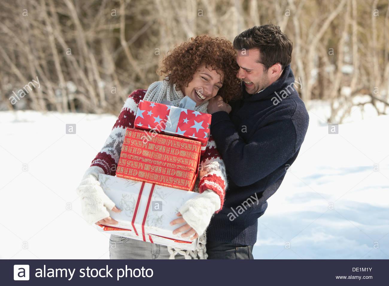 Uomo e donna con doni all'aperto, inverno Immagini Stock
