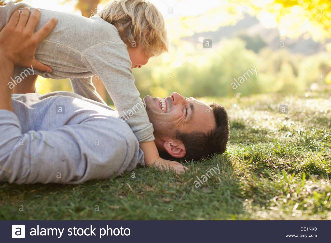 Padre e figlio posa in erba insieme Immagini Stock
