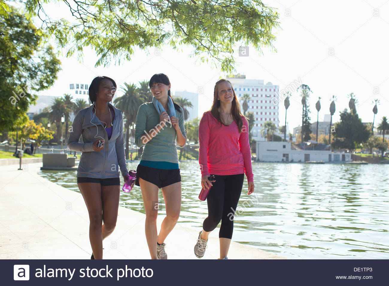 Donna che corre lungo il lago in posizione di parcheggio Immagini Stock