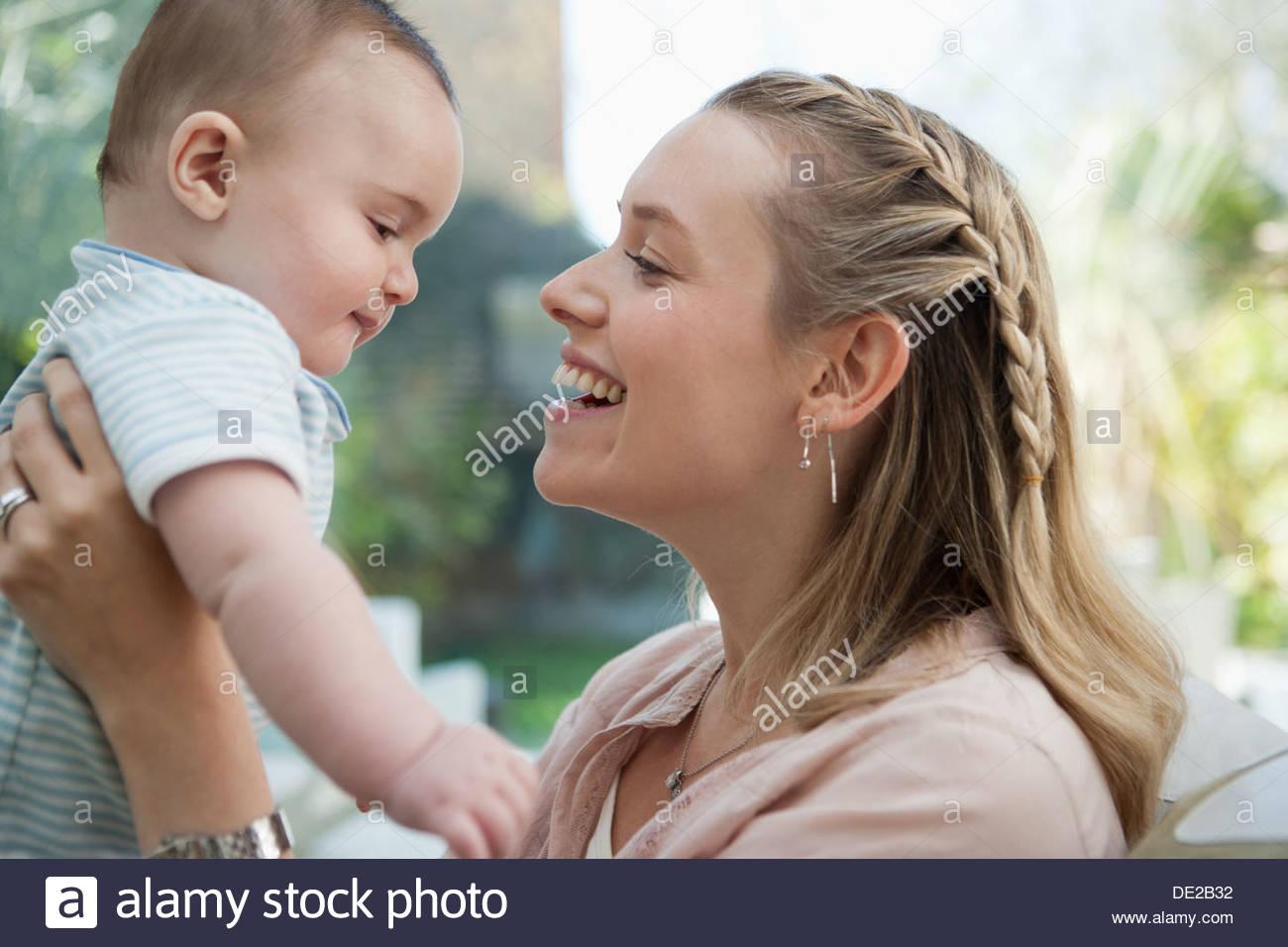 Sorridente sollevamento madre figlio bambino Immagini Stock