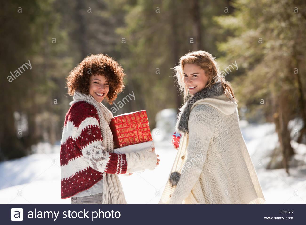 Due donne con doni all'aperto nella neve Immagini Stock