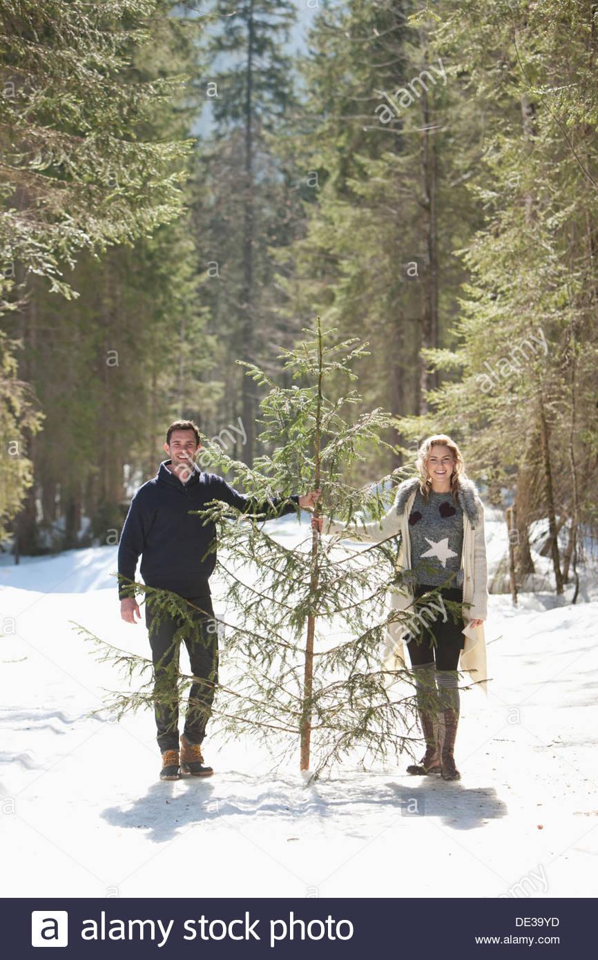 L uomo e la donna alla ricerca di albero di Natale all'aperto Immagini Stock