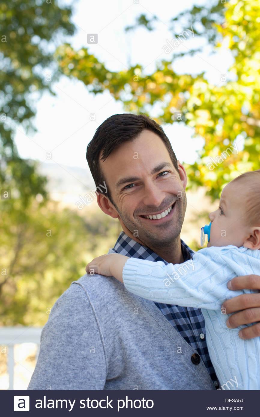 Padre sorridente holding baby all'aperto Immagini Stock