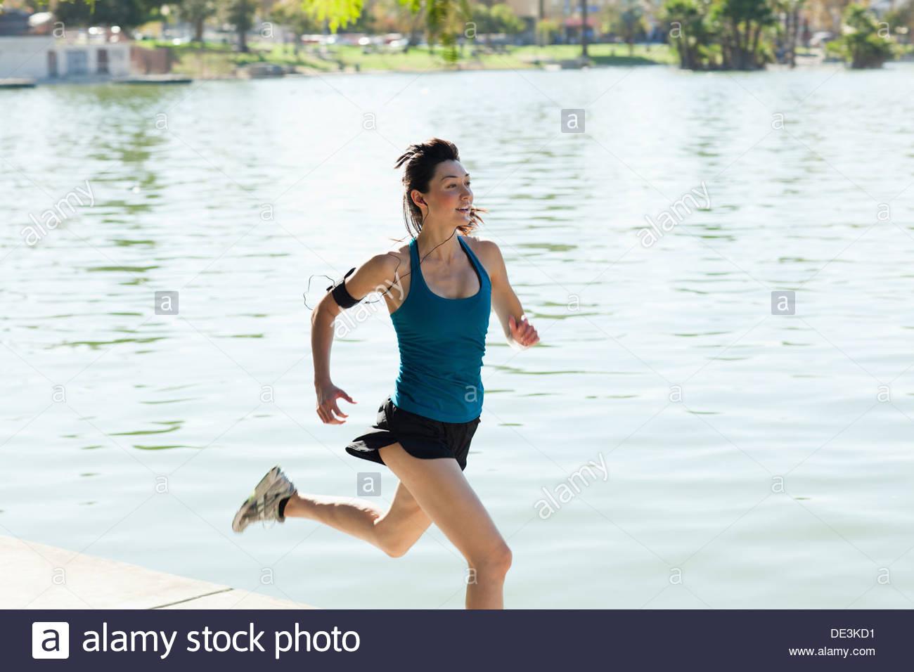 Donna che corre lungo il lago Immagini Stock