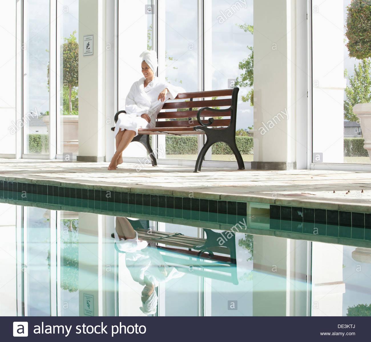 Ritratto di donna sorridente in accappatoio seduta sul banco a bordo piscina a spa Immagini Stock