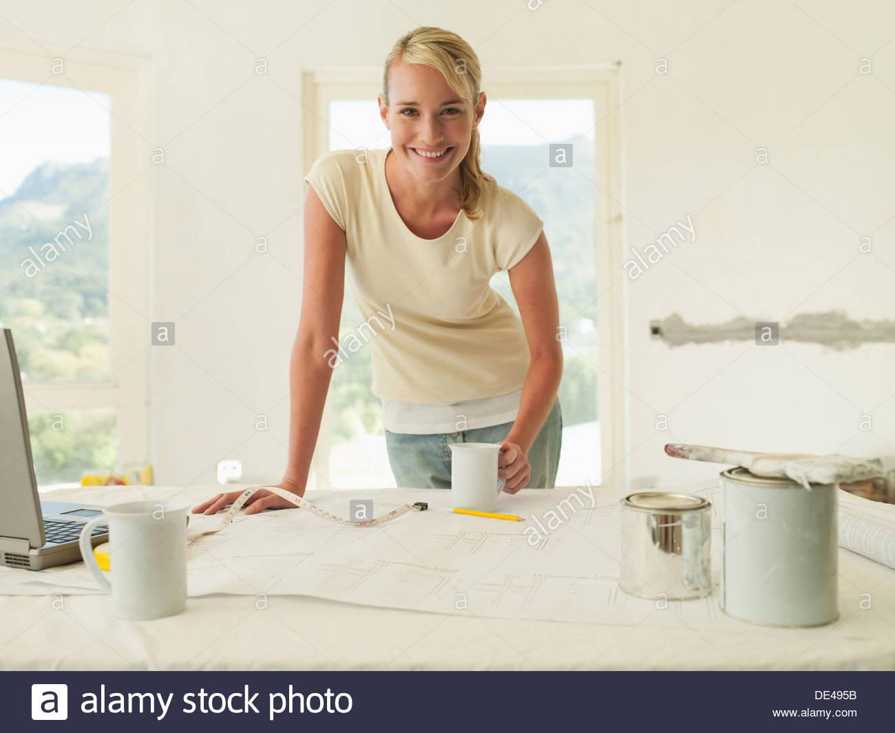 Donna sorridente appoggiato sulla tavola con blueprint e vernice Immagini Stock