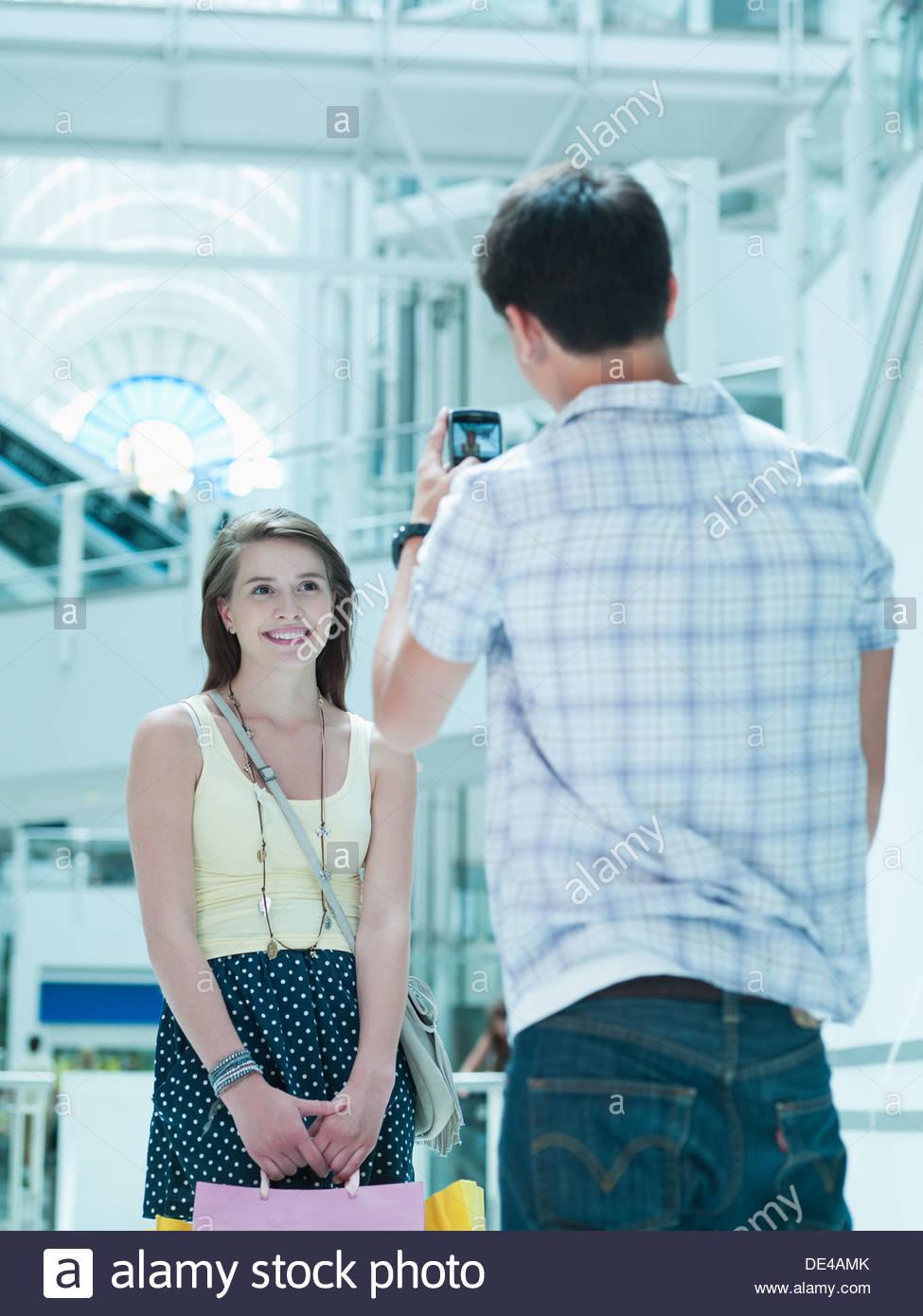 L'uomo prendendo fotografia della fidanzata nel centro commerciale per lo shopping Immagini Stock