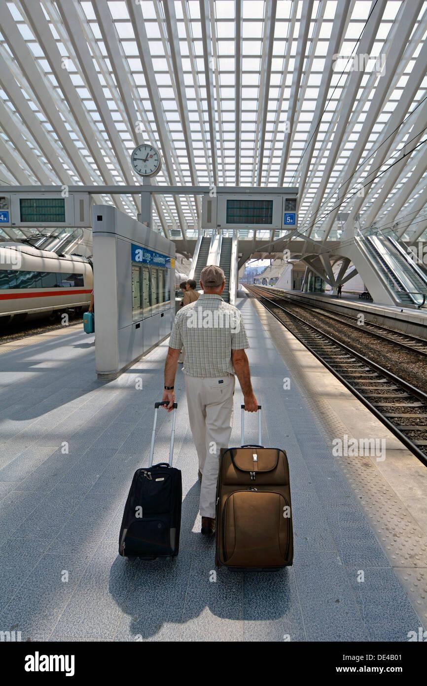 Modello di rilascio senior uomo passeggero ferroviario persona che cammina con la valigia bagaglio sulla stazione ferroviaria piattaforma di Liegi in Belgio UE moderna costruzione tetto di vetro Immagini Stock