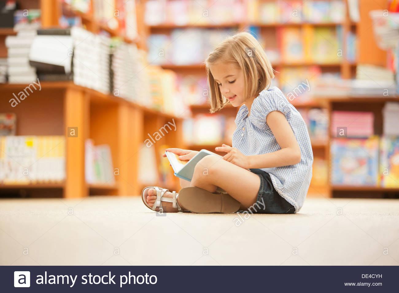 Ragazza seduta sul pavimento della biblioteca con libro Immagini Stock