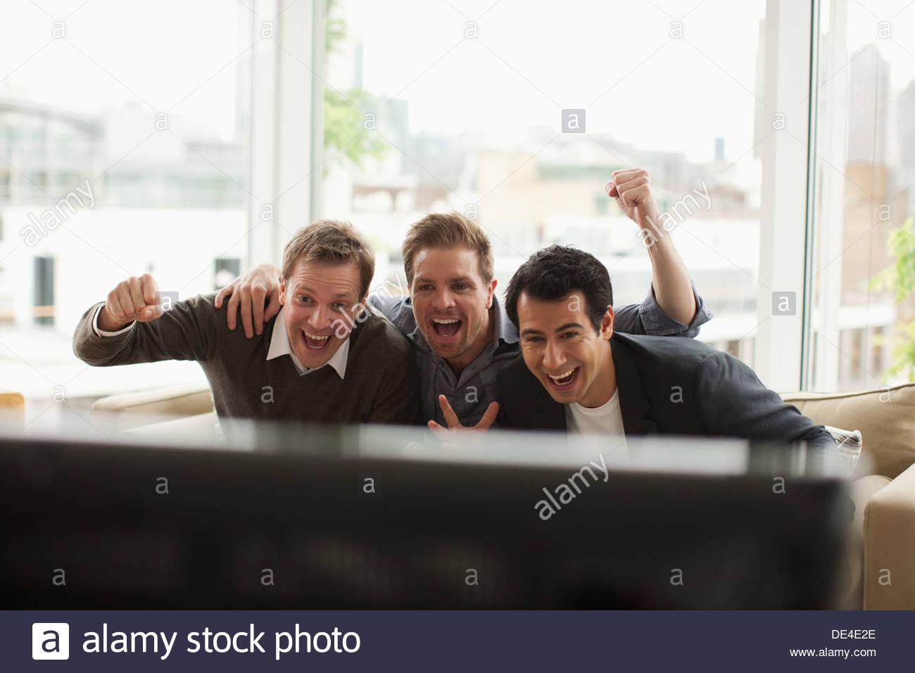 Tre uomini di guardare la televisione Immagini Stock