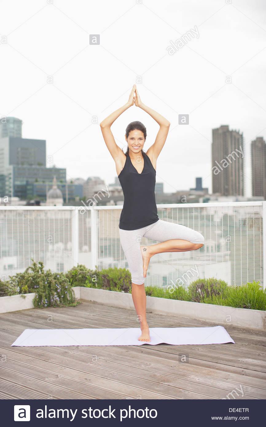 La donna a praticare yoga sulla terrazza sul tetto Immagini Stock