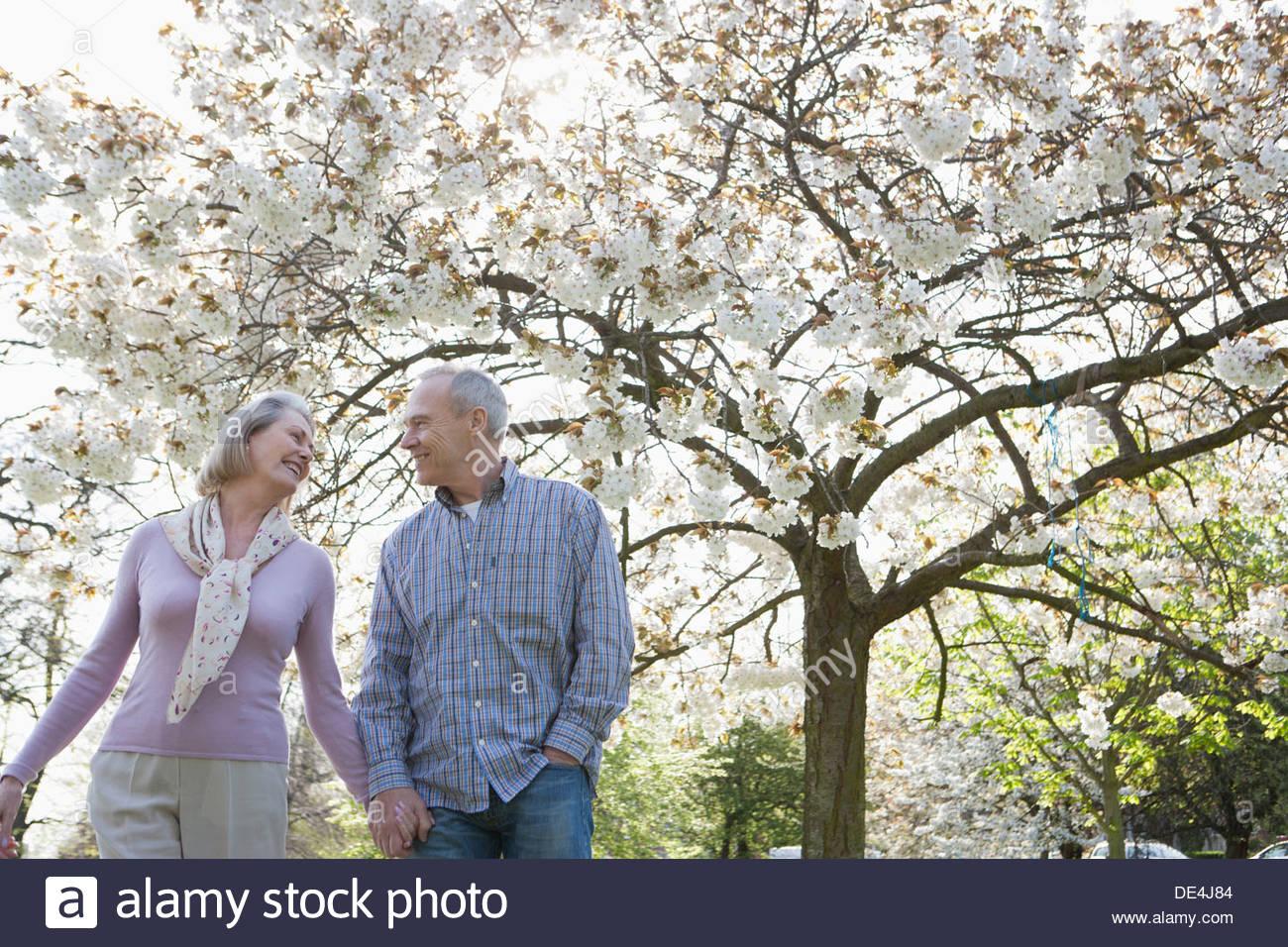 Coppia senior tenendo le mani sotto alberi in fiore Foto Stock