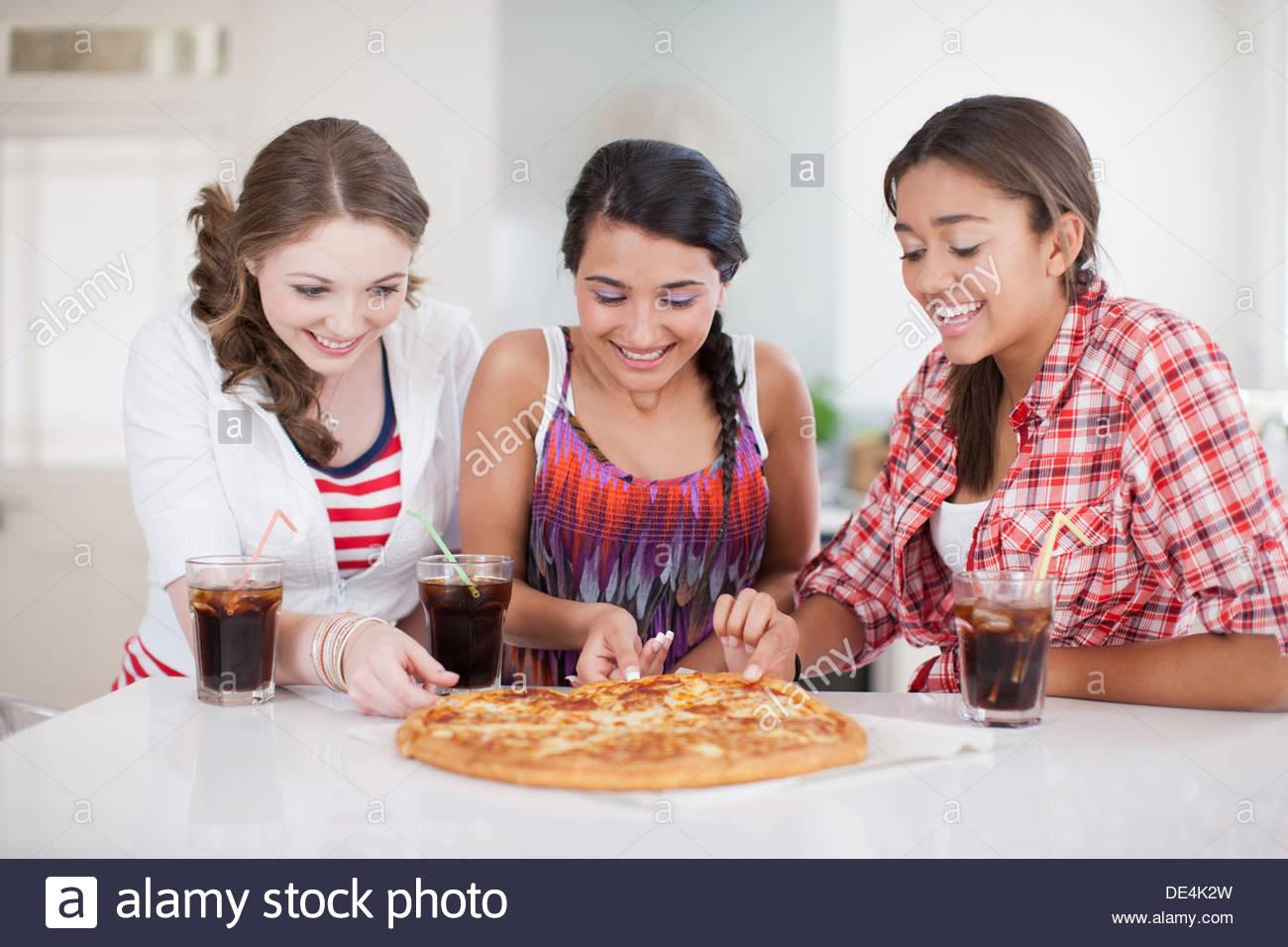 Le ragazze adolescenti mangiare la pizza Immagini Stock