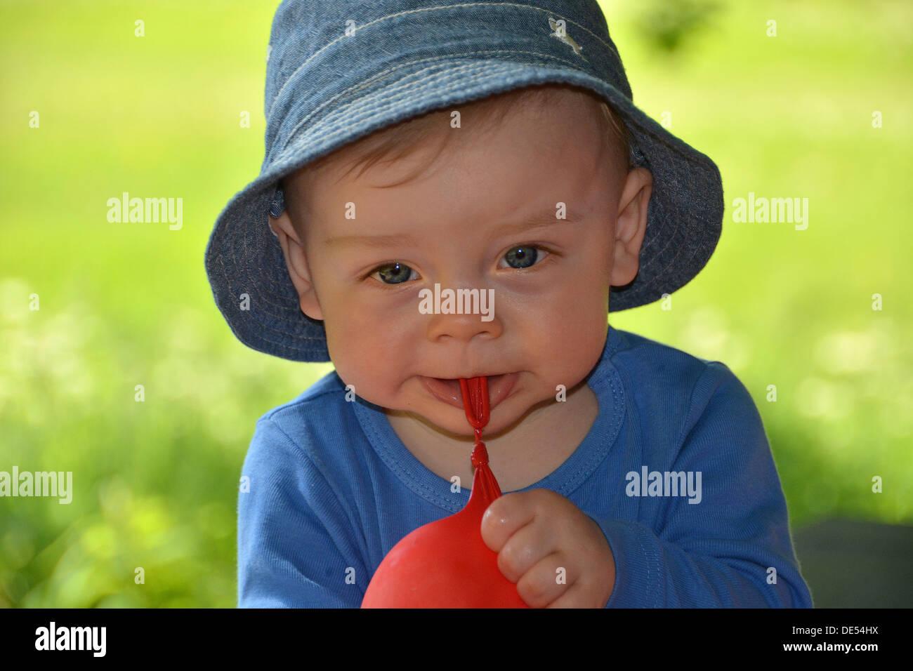 Il ragazzo, dieci mesi, giocando con un palloncino rosso all'aperto Foto Stock