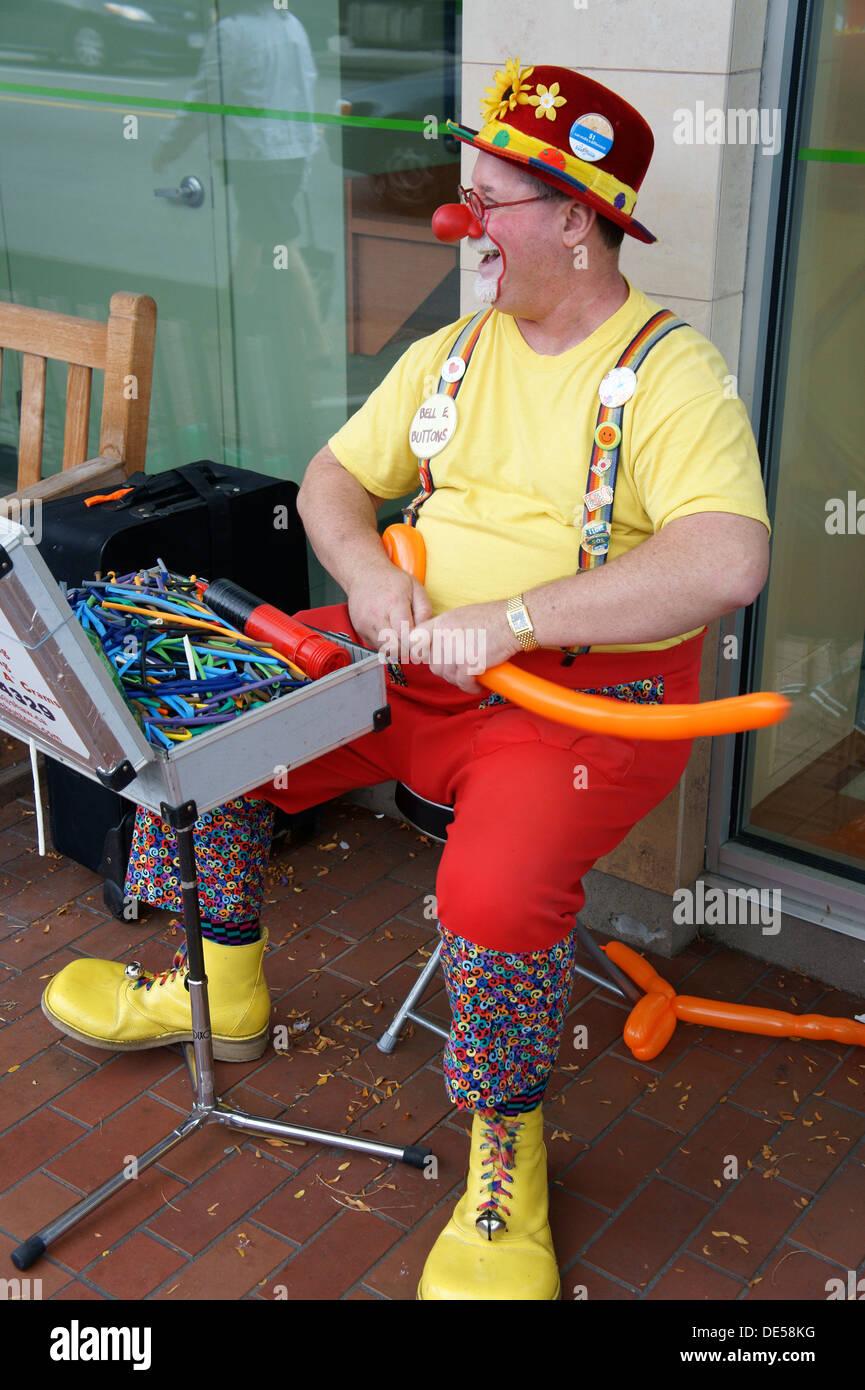 Jolly di mezza età maschio rendendo clown palloncino cappelli, Vancouver, British Columbia, Canada Immagini Stock