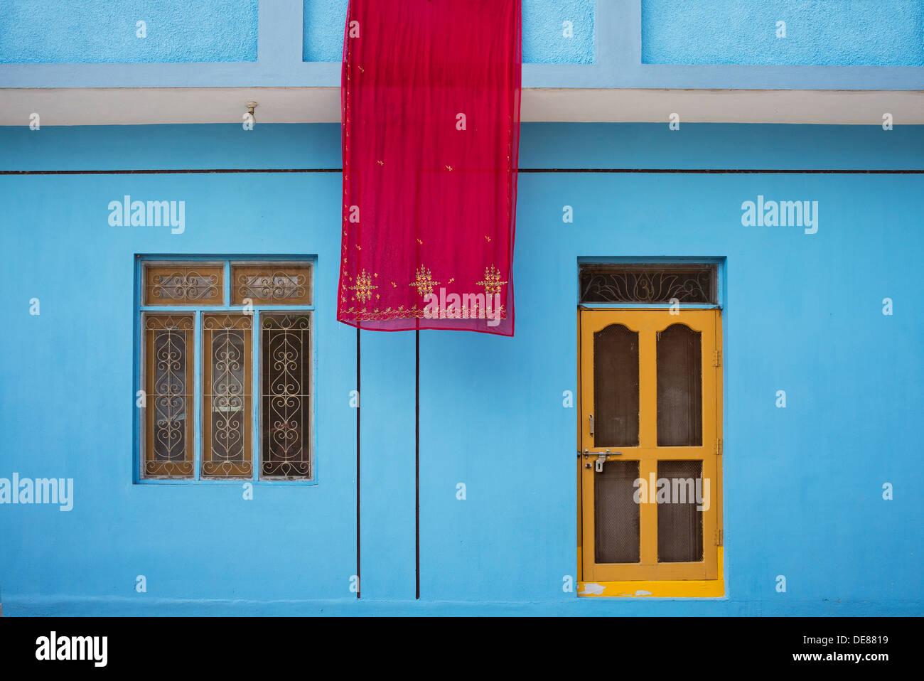 Sari indiani appendere fuori ad asciugare al di fuori di un blu rurale casa indiana. Puttaparthi, Andhra Pradesh, India Immagini Stock