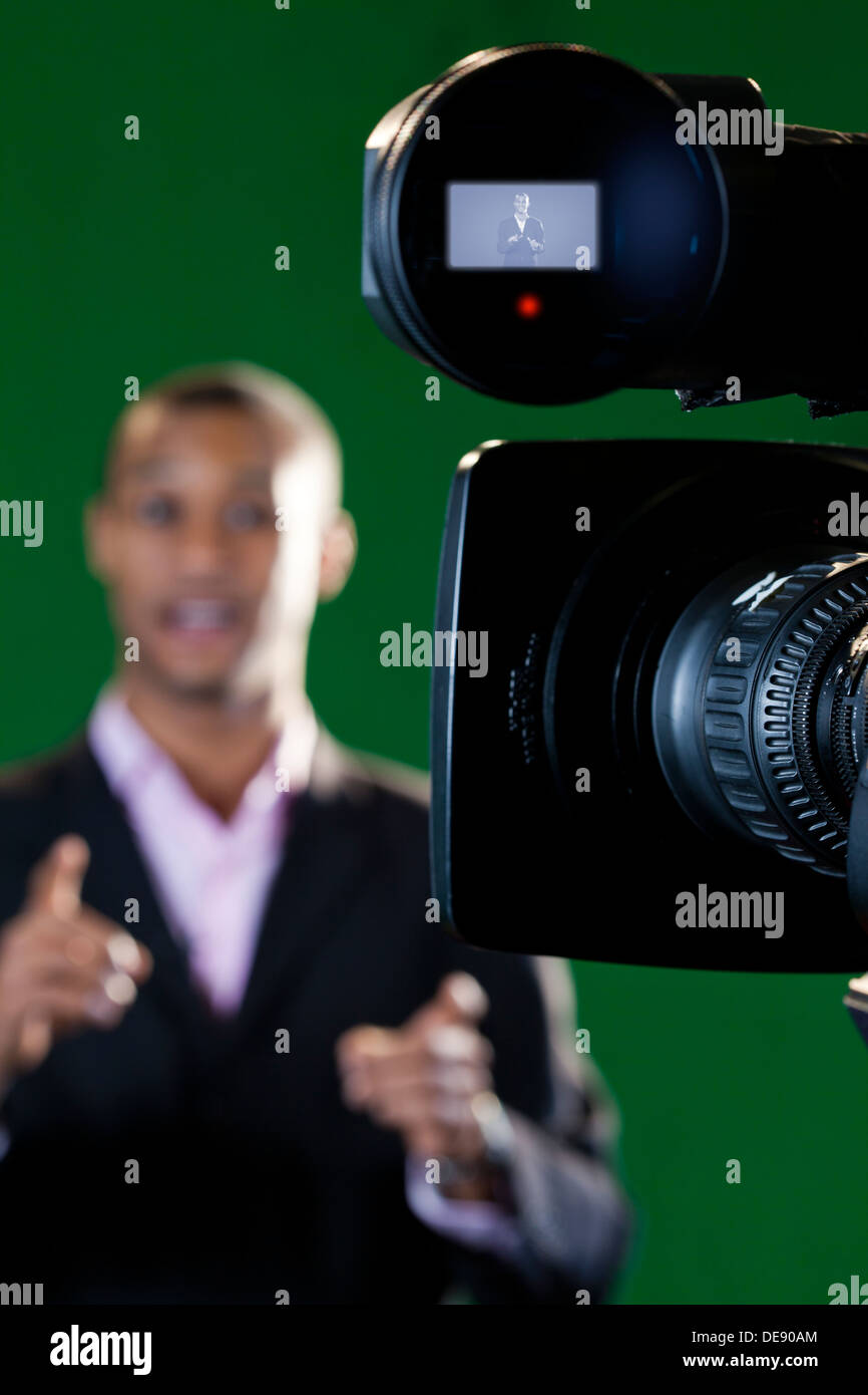 Close-up di una telecamera viewfinder e lente con un presentatore al di fuori della messa a fuoco in background. Immagini Stock