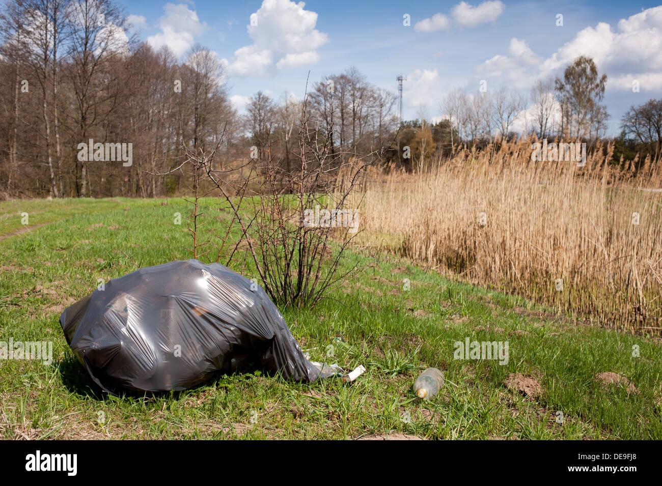 Diffusione illegale di rifiuti nel sacco nero in plastica Immagini Stock