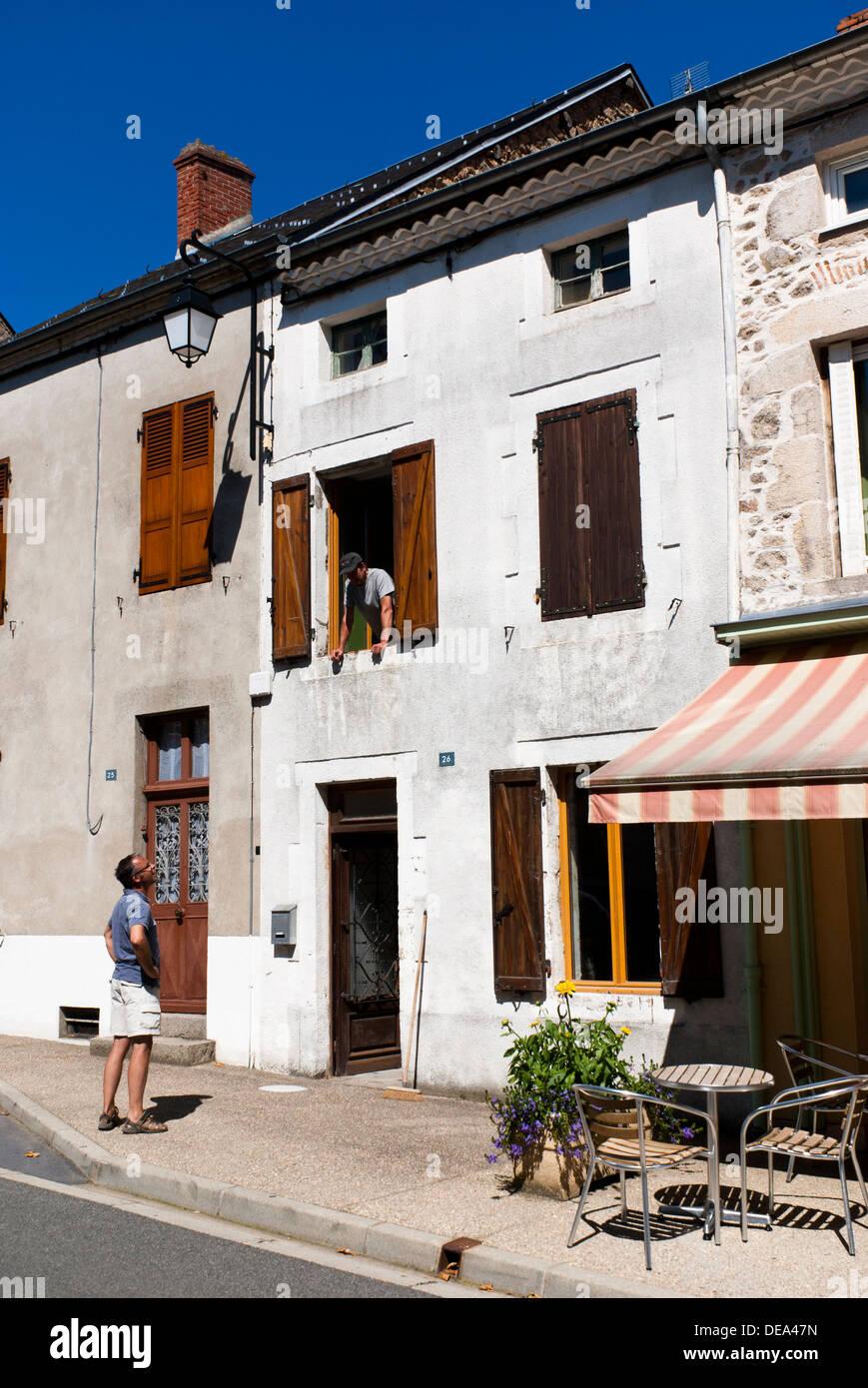 L uomo nella finestra di conversazione haviong con il prossimo in strada. Le Mayet-de-Montagne, Allier, Francia. Immagini Stock