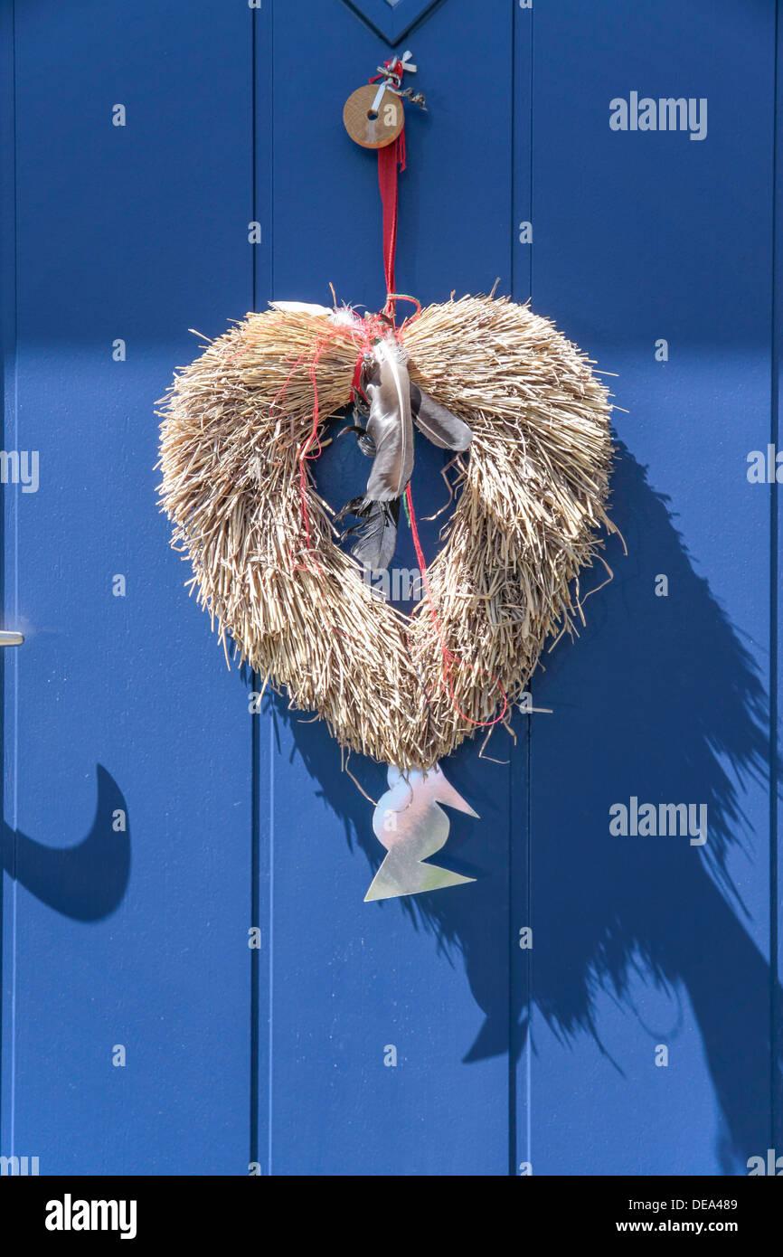 Cuore decorativo da paglia sulla porta blu in Svaneke su Bornholm. Danimarca Immagini Stock