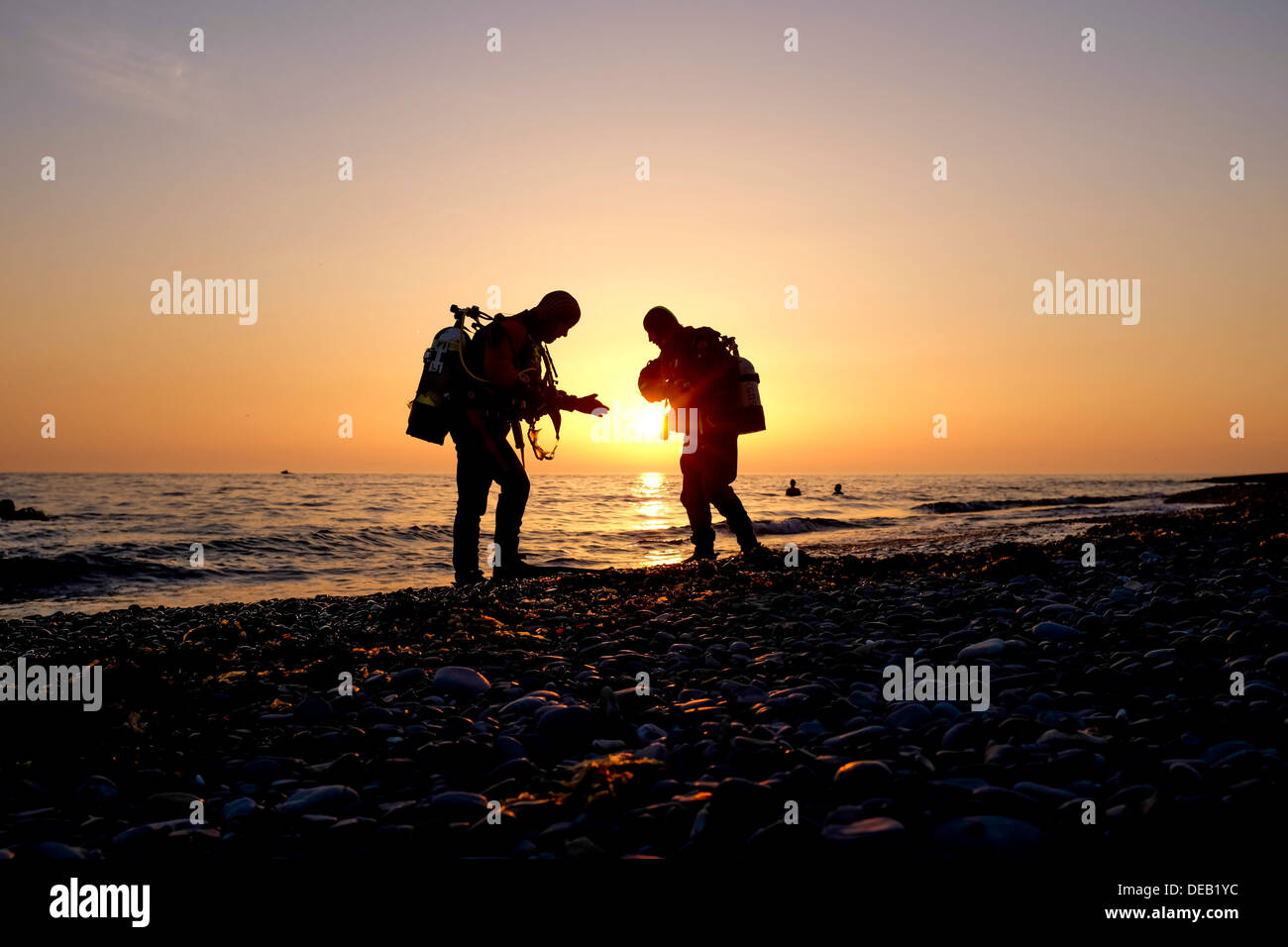 Due uomini in silhouette, scuba diving al tramonto, Cardigan Bay, Aberystwyth Wales UK Foto Stock