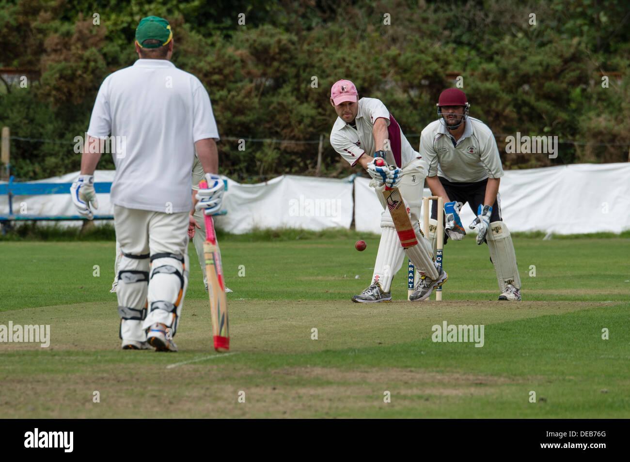 Gli uomini che giocano una domenica pomeriggio village cricket, Wales UK Immagini Stock