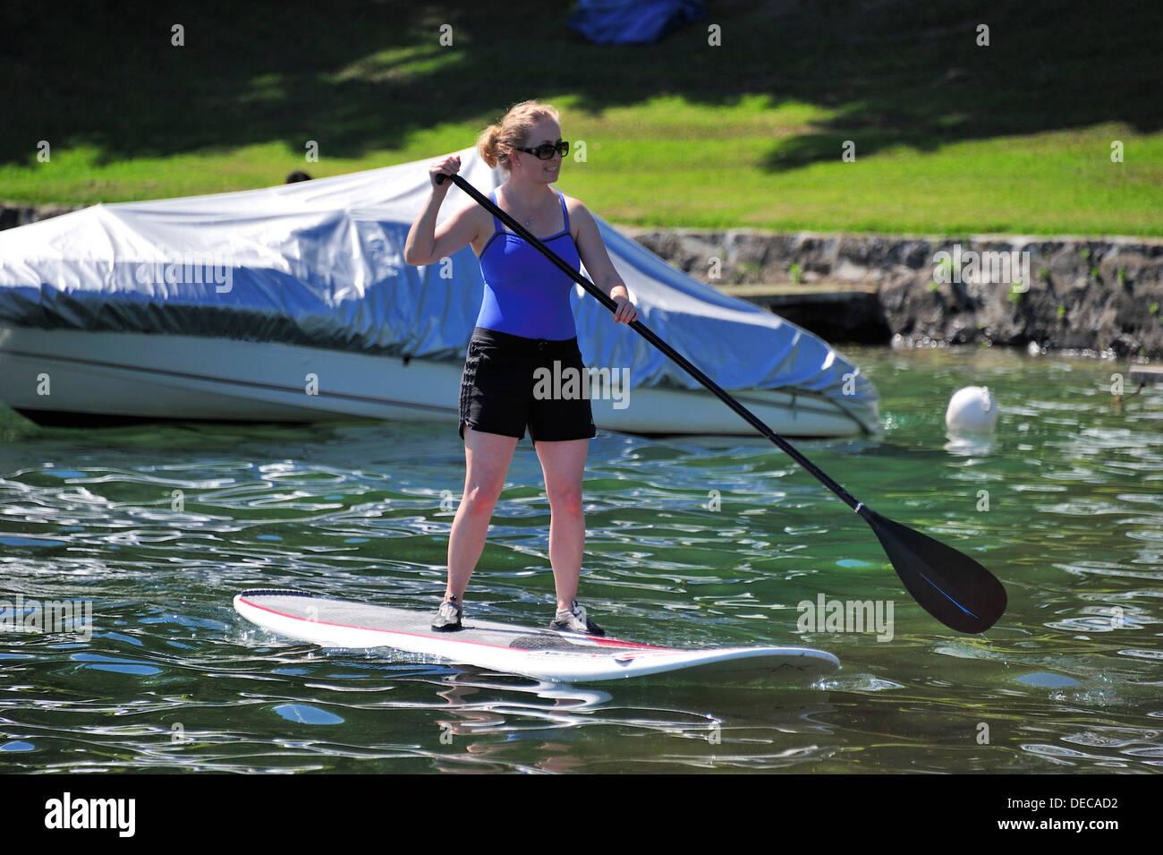 Una giovane donna su un stand-up paddleboard Immagini Stock