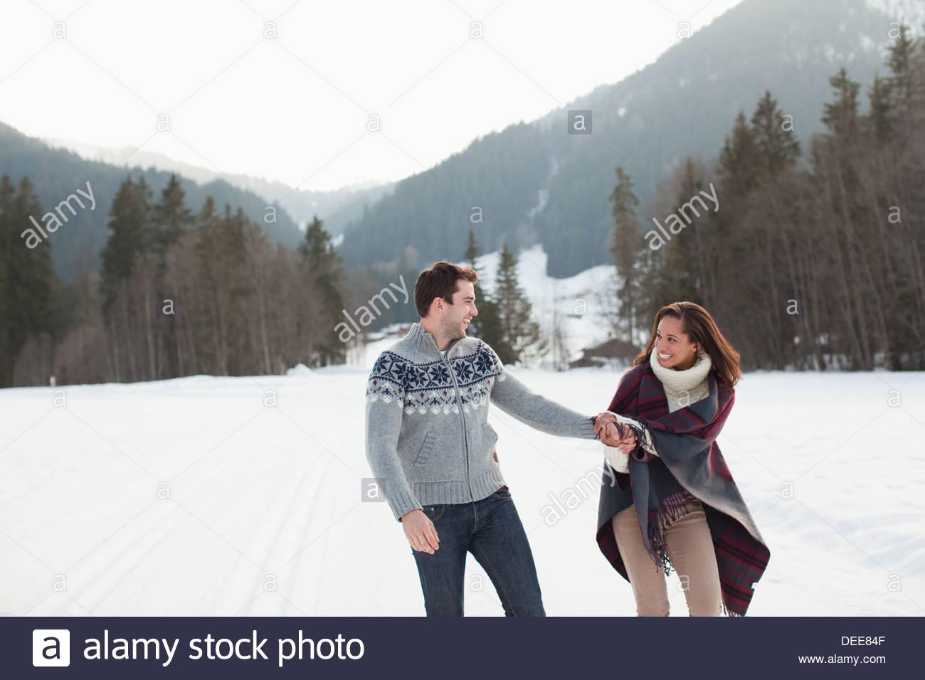 Coppia sorridente tenendo le mani e piedi nel campo nevoso Immagini Stock