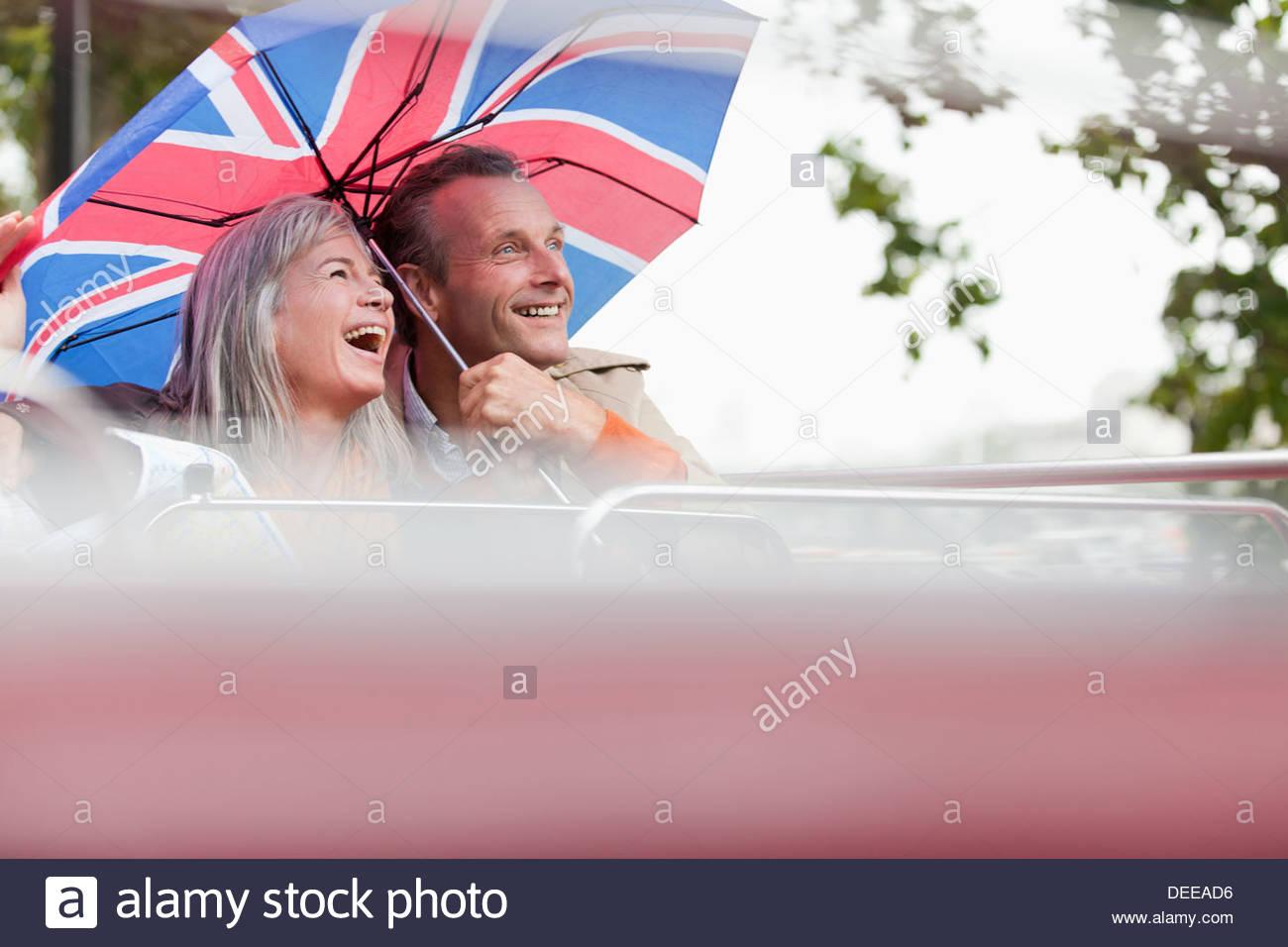 Coppia felice con la bandiera britannica di equitazione ombrello double decker bus Immagini Stock