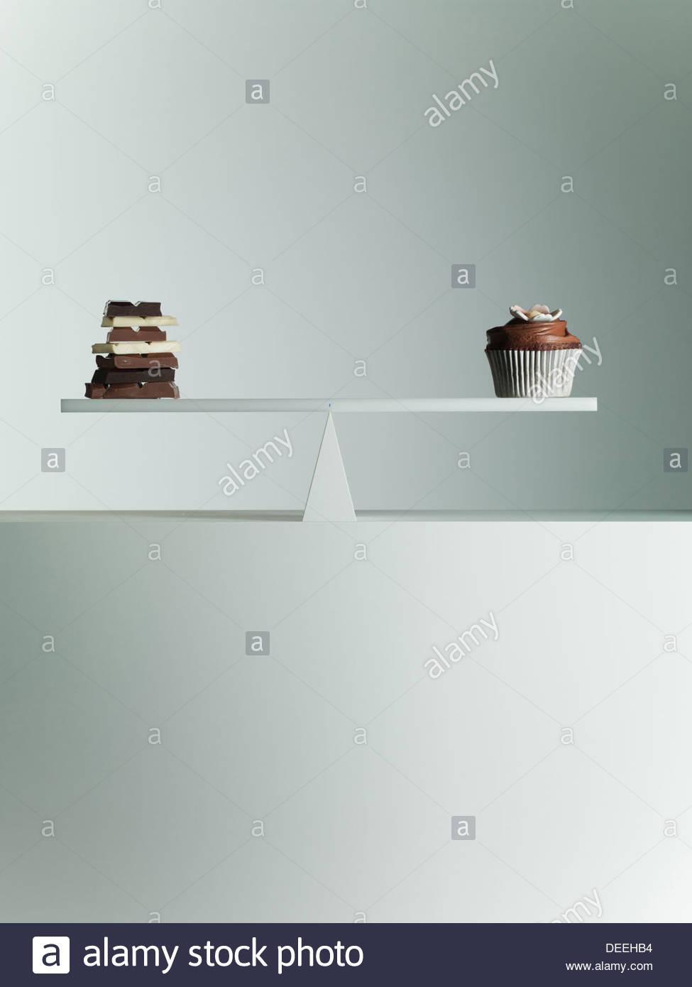 Barre di cioccolato e Tortina bilanciato su altalena Immagini Stock