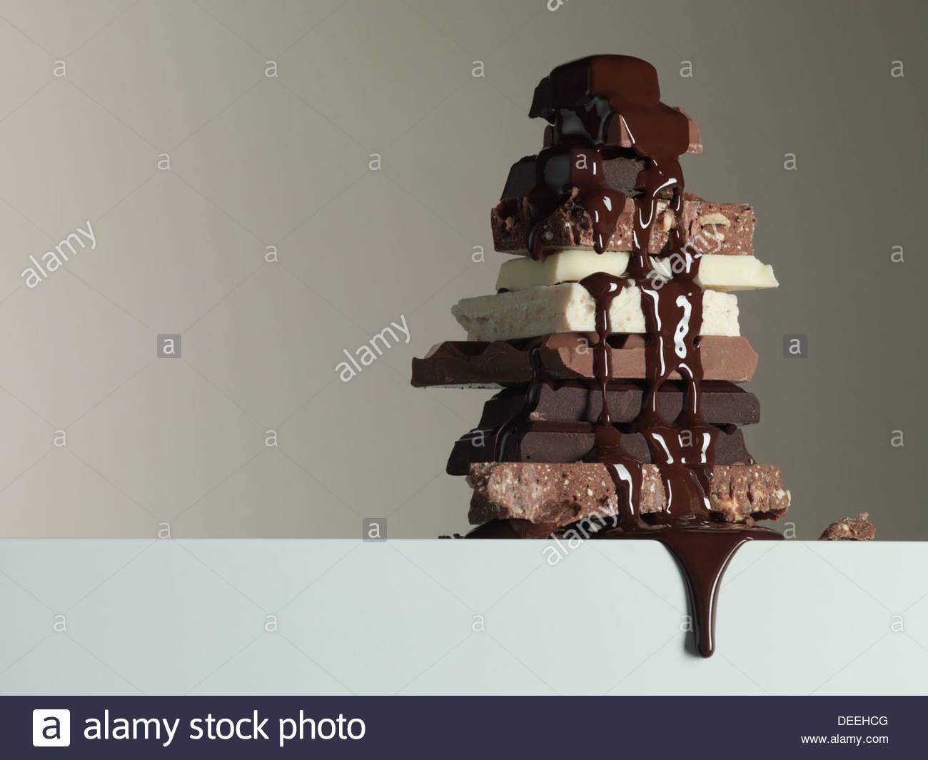 Lo sciroppo di cioccolato gocciolamento sulla pila di barrette di cioccolato Immagini Stock