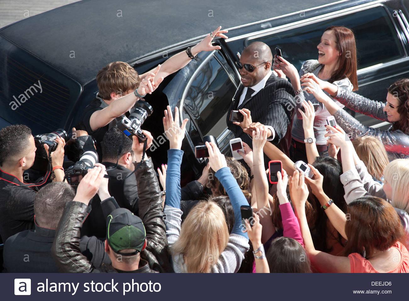 Celebrity emergente dal limo verso paparazzi Immagini Stock