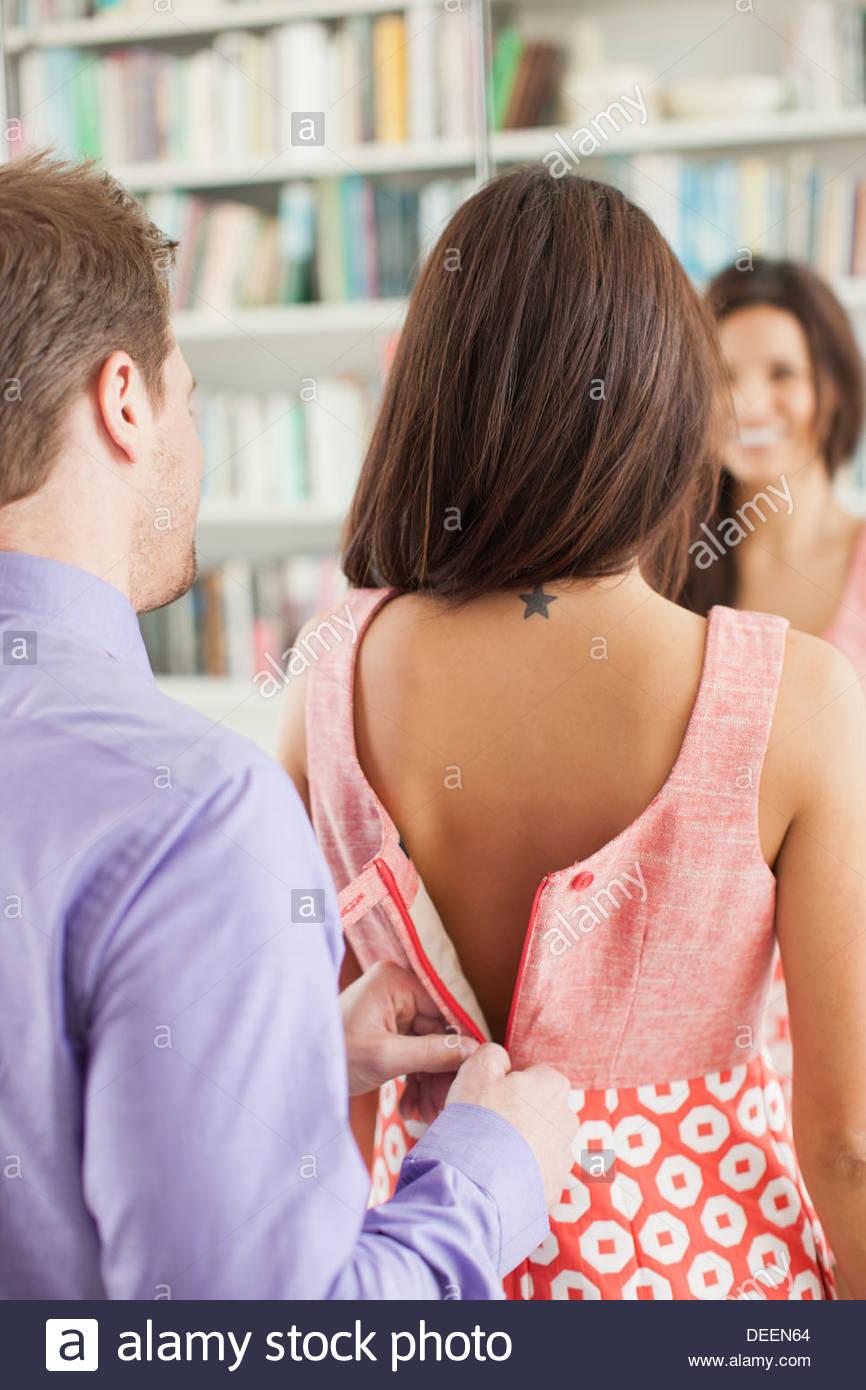 L'uomo zippare wifedel vestito per lei Immagini Stock