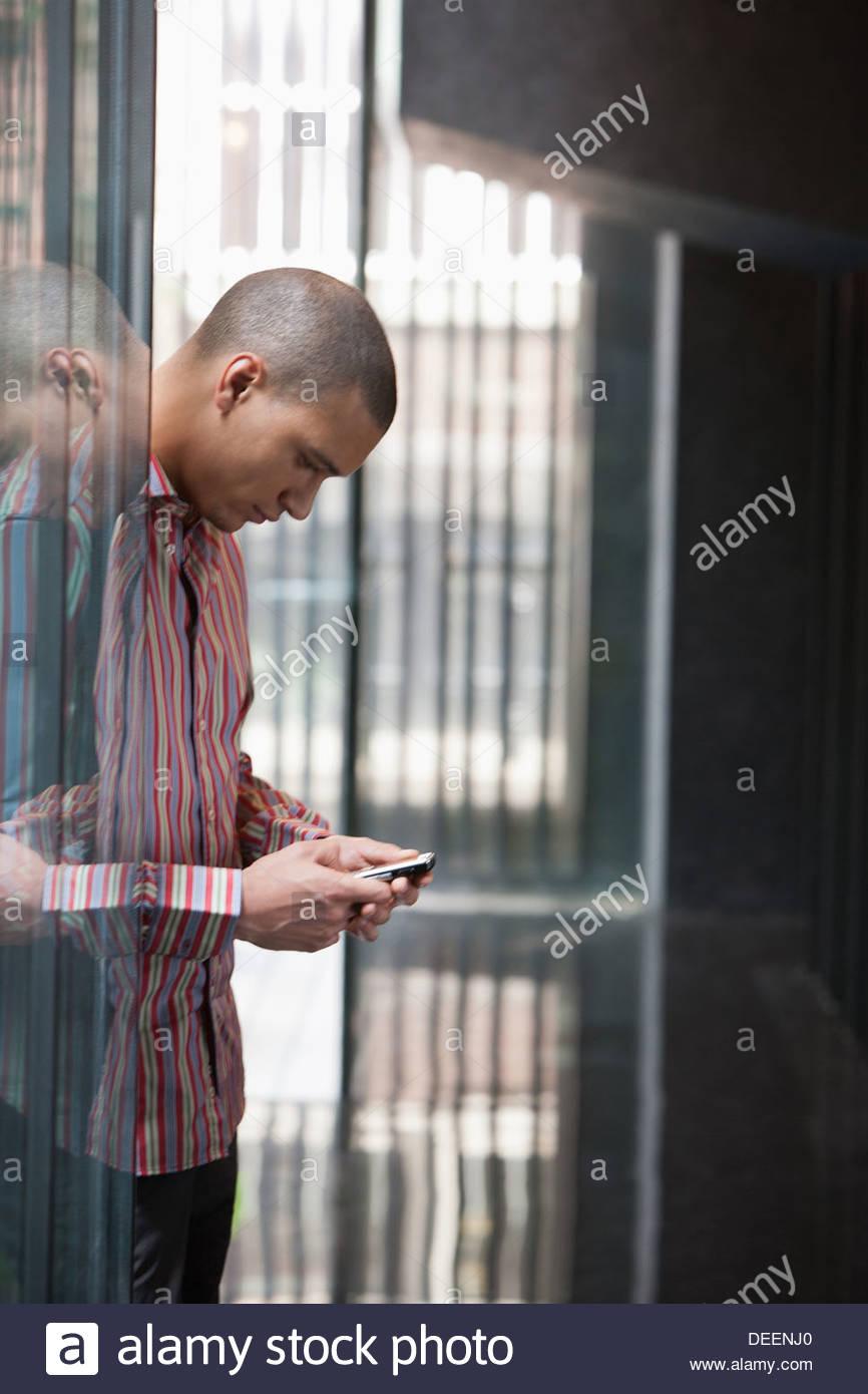 Imprenditore utilizzando il suo telefono cellulare in un ufficio Immagini Stock