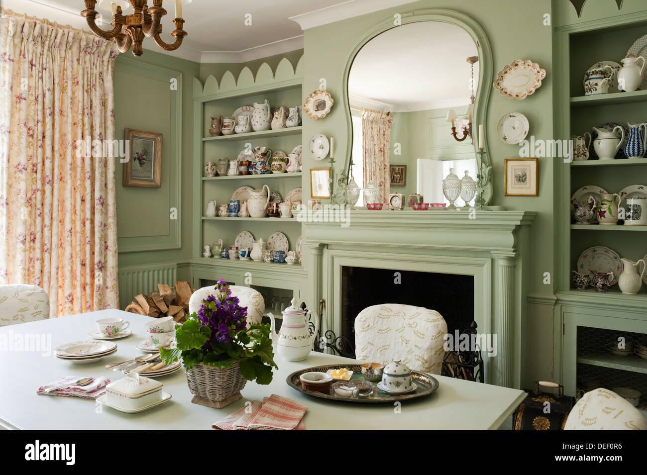 Country house la sala da pranzo con pottert raccolta su scaffalature incavata dipinta in verde pastello Immagini Stock