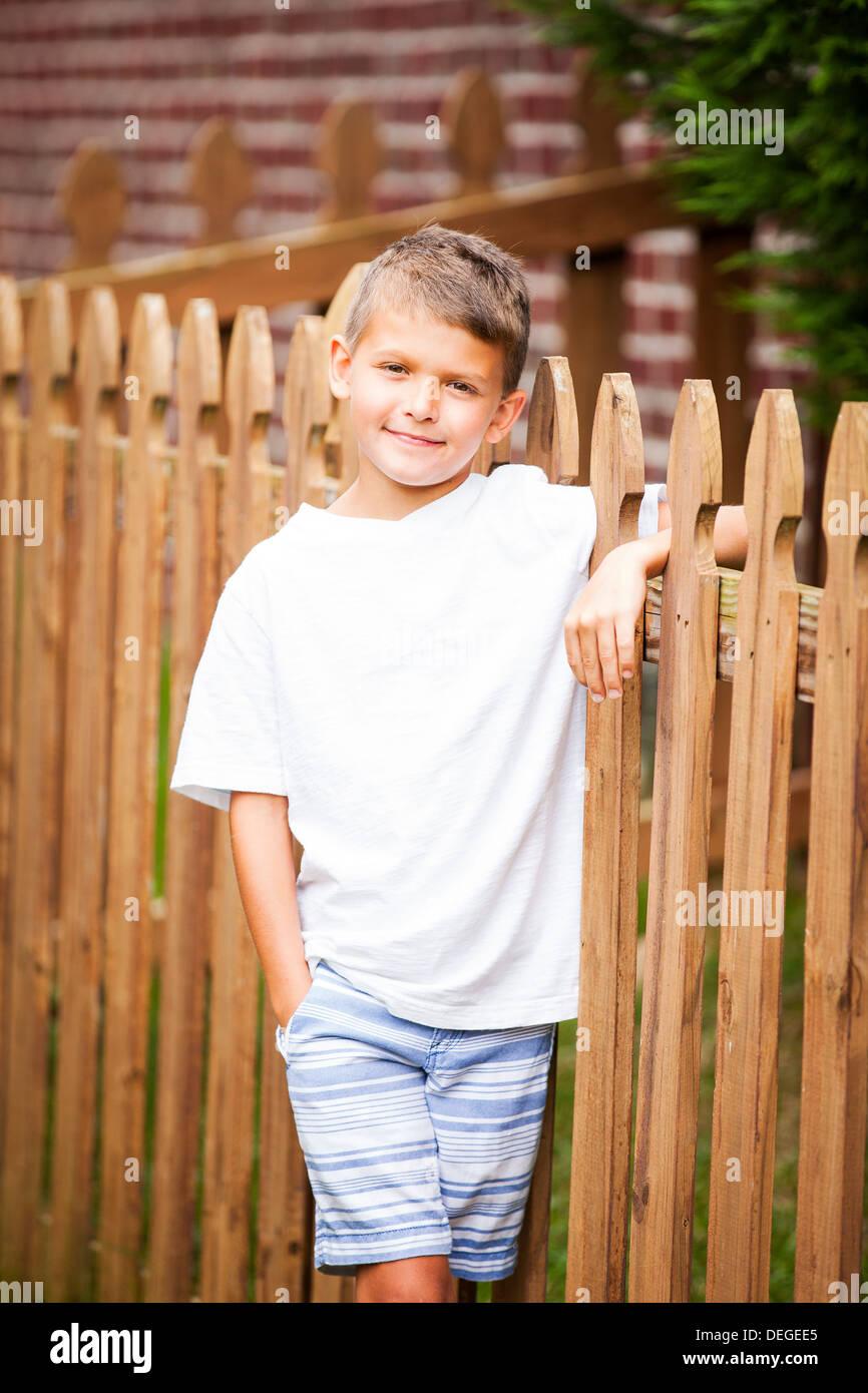 Ragazzo appoggiato su di una recinzione di legno Immagini Stock