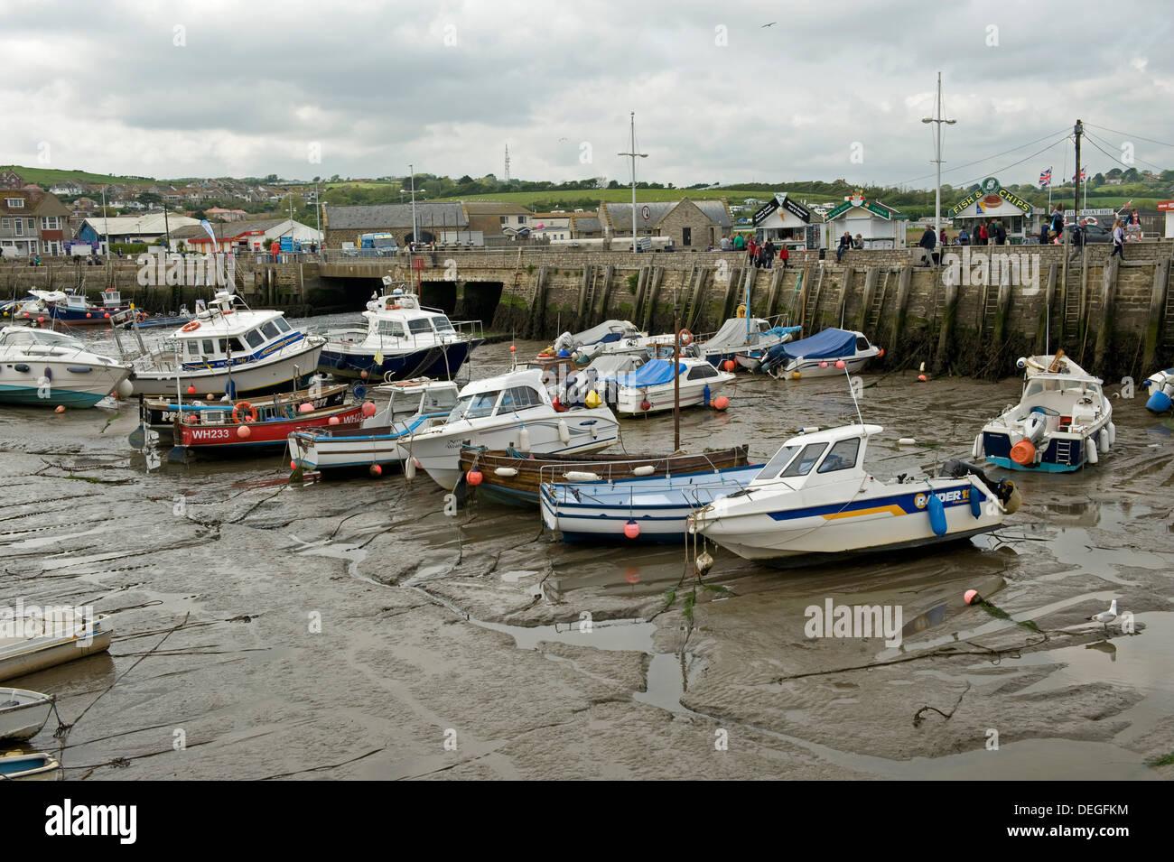 La pesca e le imbarcazioni da diporto in appoggio sul fango a bassa marea in West Bay Harbour, vicino a Bridport in Dorset, può Immagini Stock