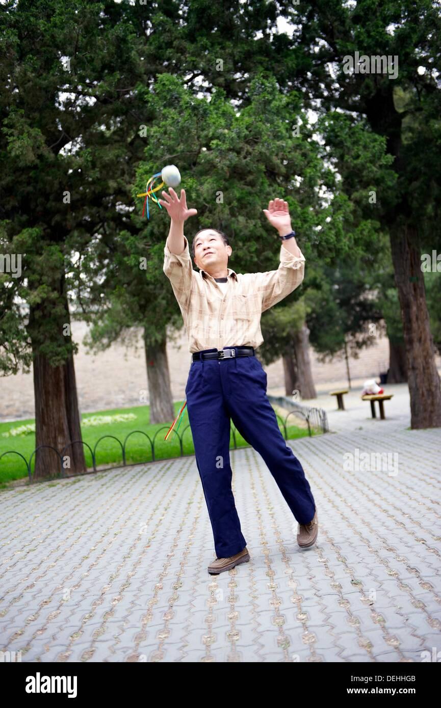 Un uomo cinese godere del tempo libero giocoleria con una borsetta nel parco pubblico di Tempio del Cielo a Pechino in Cina Immagini Stock