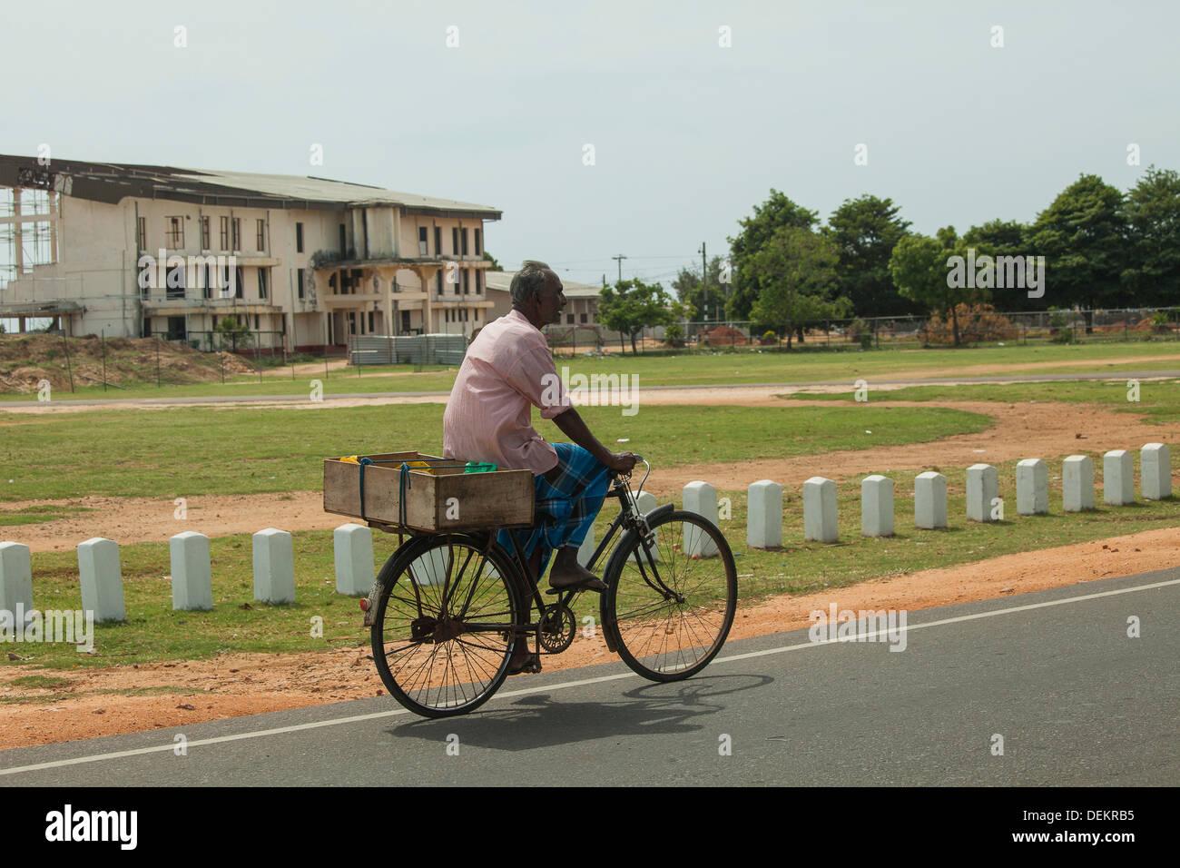 Uomo che indossa sarong su una bici in Sri Lanka Immagini Stock