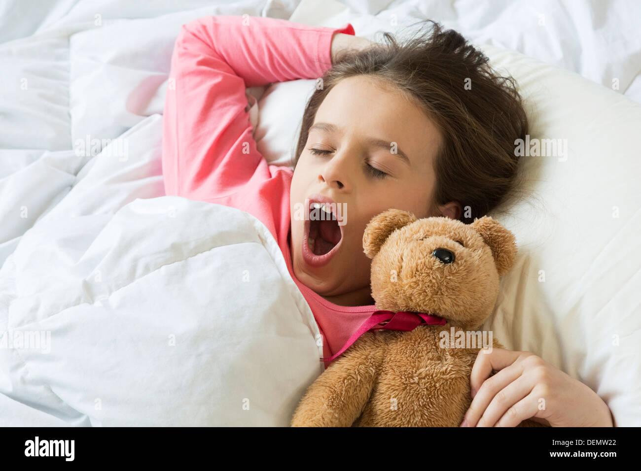 Ragazza giovane svegliarsi a sbadigliare a letto Immagini Stock